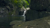 montanhas rochosas : Mountain waterfall in jungle. Stream water from waterfall flowing on large stones in river.