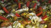 rice pan : Traditional spain food paella with mussels, shrimps, calamari and vegetables in pan. Close up. Cooking spanish paella with red hot peppers and fresh seafood in pan close up.