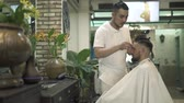Hair cutter doing male hairstyle with electric razor in barber shop. Man getting haircut in hairdressing salon. Professional hairstylist cutting hair in male salon. Man hairdressing with electric shaver.