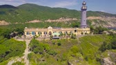 Light house on mountain cliff on sea shore aerial view. Beautiful landscape sea lighthouse on green mountain and blue water drone view. Stok Video