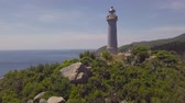 Sea lighthouse on green mountains and rocky shore drone view. Aerial view light house on mountain cliff and turquoise sea landscape. Stock Footage