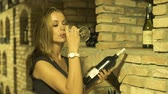 Young woman drinking red wine from glass and looking bottle in cellar. Woman winemaker tasting and drinking red wine from glass in traditional cellar. Stok Video