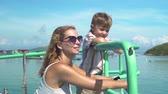 vztahy : Happy mom and little son aboard sailing ship in sea cruise. Young mother together son traveling on ship sailing in cean while summer vacation. Dostupné videozáznamy