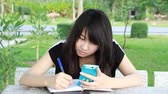 book : Portrait of thai student teen beautiful girl using her smart phone and write a book sitting in park.