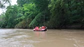 rubber tubing : tourist paddling on rubber boat at forest river in thailand