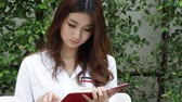 red : Portrait of thai adult beautiful girl white shirt reading red book