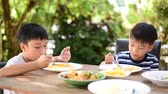 bowl : Young Thai boy eating with food on the wooden table with his family in the garden. And out focus tree background.