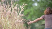 relaxation : Slow motion of Young girl riding bicycle in the park and touch flower of grass