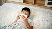harcamak : Young Asian boy using smartphone and listen to earphone on the white bed. Stok Video