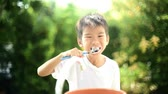 dişler : Slow motion, selective focus at Young asian Thai boy brush his teeth in a garden with beautiful green bokeh from green leaf.