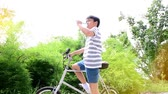 bisiklete binme : Slow motion of Preteen Asian Thai boy drinking water from plastic bottle during cycling on a bike in a garden.