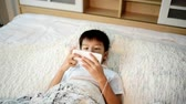 money thai : Young Asian boy using smartphone and listen to earphone on the white bed. Stock Footage