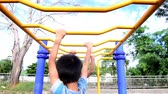 младенец : Pree teen play with a yellow hang bar in a park during summer day. Стоковые видеозаписи