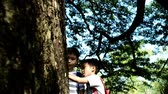 szczęście : Two asian boy looking at a big tree in a park Wideo