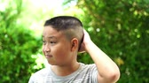 barber hair cut : Slow motion young Asian boy feel comfortable with short hair cut style Stock Footage