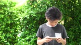 zongora : Slow motion young Asian boy user phone at home garden