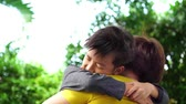 sarılma : Young Asian Thai boy hug his mom with love in a garden.