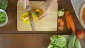 pimenta : Top view of woman chief making salad healthy food and chopping bell pepper on cutting board in the kitchen.