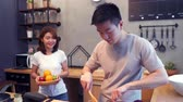an : Asian man prepare salad food in the kitchen. Beautiful happy asian couple are cooking in the kitchen. Young asian couple have romantic time while staying at home. Couple lifestyle at home concept. Stok Video