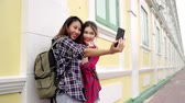 blogger : Traveler backpacker Asian women lesbian lgbt couple travel in Bangkok, Thailand. Happy blogger young female couple using smartphone for selfie.