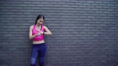 Healthy beautiful young Asian Athlete woman setting and checking progress looking heart rate monitor on smart watch while running in urban city. Lifestyle women exercise in the city concept. Stock Footage