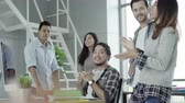 Successful handsome smart Asian creative businessman and his colleagues arms raised celebrating success Operating Result feeling happy in office. Lifestyle business man in his workplace concept. Stock Footage