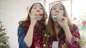 Slow motion - Happy Asian women celebrate christmas party with friends in office. Female celebrating New Year and Christmas Festival together. Group of beautiful people in Santa hats dance in office.