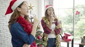 Happy Asian women celebrate christmas party with friends in her office. Female celebrating New Year and Christmas Festival together. Girls wear santa hats drink alcohol in office.