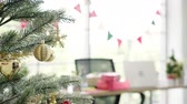 Happy Asian woman holding xmas ornament for decorate christmas tree in her office. Attractive female and her friends spend holiday celebration. Winter holidays concept. Stock Footage