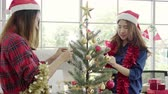 Happy Asian women holding xmas ornament for decorate christmas tree in her office. Attractive female and her friends spend holiday celebration. Winter holidays concept. Stock Footage