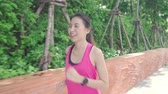 марафон : Healthy beautiful young Asian runner woman in sports clothing running and jogging on street in urban city park. Lifestyle fit and active women exercise in the city concept. Стоковые видеозаписи