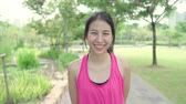 Healthy beautiful young Asian runner woman feeling happy smiling and looking to camera after running on street in urban city park. Lifestyle fit and active women exercise in the city park concept.
