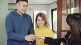 real estate sign : Happy young Asian couple and realtor agent. Cheerful young man signing some documents and handshaking with broker while sitting at desk. Signing good condition contract.