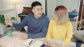 recibo : Young stressed asian couple managing finances, reviewing their bank accounts using laptop computer and calculator at modern home. Woman and man doing paperwork together, paying taxes online.