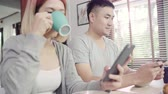 Attractive young Asian couple distracted at table with newspaper and cell phone while eating breakfast. Excited young Asian couple surprised by unbelievably good news, happy family amazed by internet.