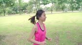 Slow motion - Healthy beautiful young Asian runner woman in sports clothing running and jogging on street in urban city park. Lifestyle fit and active women exercise in the city concept.
