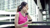 Healthy beautiful young Asian Athlete woman using smartphone for listen to music while running in urban city. Lifestyle women exercise in the city concept.