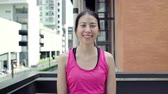 independent : Healthy beautiful young Asian runner woman feeling happy smiling and looking to camera after running on street in urban city. Lifestyle fit and active women exercise in the city concept.