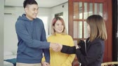 imzalama : Happy young Asian couple and realtor agent. Cheerful young man signing some documents and handshaking with broker while sitting at desk. Signing good condition contract.