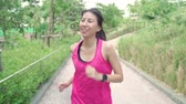 izlemek : Slow motion - Healthy beautiful young Asian runner woman in sports clothing running and jogging on street in urban city park. Lifestyle fit and active women exercise in the city concept.