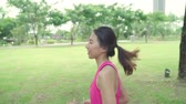 maratona : Slow motion - Healthy beautiful young Asian runner woman in sports clothing running and jogging on street in urban city park. Lifestyle fit and active women exercise in the city concept.
