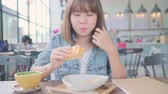 ハンバーガー : Business freelance Asian woman eating bread and drinking warm cup of coffee while sitting on table in cafe. Lifestyle smart beautiful female relax in coffee shop concepts.