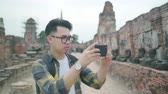 исследовать : Traveler Asian man using smartphone for take a picture while spending holiday trip at Ayutthaya, Thailand, Male enjoy his journey at amazing landmark in traditional city.