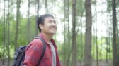 исследовать : Hiker Asian backpacker man on hiking adventure feeling freedom walking in forest, Male enjoy his holidays near lots of tree. Lifestyle men travel and relax in freetime concept.