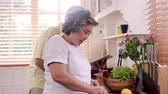 salata : Asian elderly couple cut tomatoes prepare ingredient for making food in the kitchen, Couple use organic vegetable for healthy food at home. Lifestyle senior family making food at home concept. Stok Video