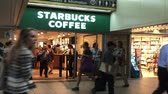 купить : New York, June 17, 2017: People walk in and out of a Starbucks store at Pennsylvania Station as other commuters walk by. Стоковые видеозаписи