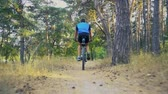 bisikletçi : bearded man cyclist rides in the forest on a mountain bike.