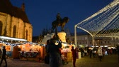 безделушки : CLUJ-NAPOCA, ROMANIA - DECEMBER 5, 2015: Unidentified people shop for Christmas at traditional market chalets. Christmas lights in the evening. Стоковые видеозаписи