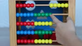 калькулятор : Child playing with wooden abacus