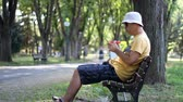 freuen : Man in hat and sunglasses using smartphone in park on the bench. Man using smartphone while relaxing in the park
